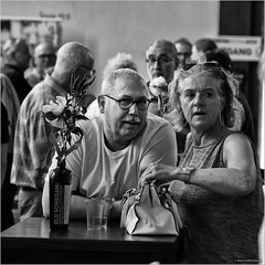Old Schiedam (John Riper) Tags: johnriper street photography straatfotografie schiedam square bw black white zwartwit mono monochrome netherlands candid john riper canon 6d 24105 l cultural event jenever genever gin jeneverfestival lady gentleman smile surprised eye contact flower bottle vase people public earrings