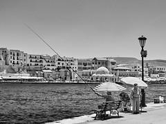 Casting (rasmusthepood) Tags: summer greece chania harbor harbour fisherman parasol oldtown monochrome blackandwhite street