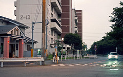Intersection with a koban (odeleapple) Tags: nikon f100 af nikkor 50mm kodakektar100 film koban intersection vehicle twilight building