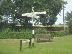 Mill Road / Church Road, Sutton, Norfolk (LookaroundAnne) Tags: gwuk signpost norfolk sutton bench