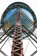 rusty water tower 4 life (primemundo) Tags: watertower rusty lookingup blue circle rivets geometric symmetry symmetrical bigblue