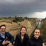 Dr. Goldberg poses with students on a bridge overlooking a canal in Greece.