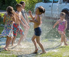 Staying cool (femmaryann) Tags: children playing water splashing summer fun swimming trunks costumes soaking outdoors grass fete holiday laughter