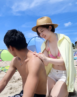 Young woman applying sunscreen to boyfriend