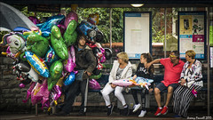 The Balloon man sheltering (zolaczakl) Tags: photographybyjeremyfennell nikond7100 nikonafsnikkor24120mmf4gedvrlens people candid streetscenes upfest2017 balloon 2017 july busstop busshelter bristol uk england rain southwest streetart graffiti event