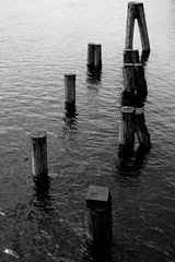 Bollards (Von Noorden her) Tags: bollards pfosten post posts water waves bw blackandwhite black white shade schatten dark grey sea habour hafen wasser trave deutschland germany
