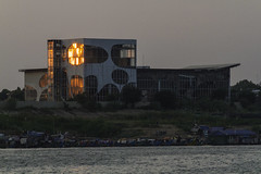 Not sure what this building is? (Keith Kelly) Tags: asia bassacriver boat cambodia cruise kh kampuchea mekongriver phnompenh seasia southeastasia tonlesap architecture aroundtown building capital city glass metal ride river sunset water windows