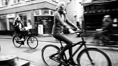 On their way... (jaap spiering | photo projects int.) Tags: jaapspiering jaapspieringphotographer jaapspieringfotografie blackandwhite monochrome zwartwit bw noiretblanc bnw streetphotography street people mens mensen bike denhaag gx8 070 woman vrouw women vrouwen femmes femme holland