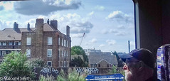 The Man On The Train (M C Smith) Tags: man train view london flats skip clouds white sky blue graffiti wall housing crane bushes green buildings window seat