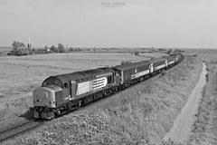 37419 approaches Stracey Arms working 2P21 1317 Great Yarmouth - Norwich 19/7/2017. Got numerous colour shots at this location, so tried a B&W version for a change. (Paul-Green) Tags: class 37 374 37419 37405 nc37 stock drs direct rail services stracey arms a47 acle straight aga abellio greater anglia passenger service july 2017 canon camera flickr outdoor black and white picture photography railways filed windmill landscape norfolk english electric type 3 diesel engine 2p21 1317 gt great yarmouth norwich