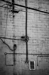 We Appear to Have our Lines Crossed (Katrina Wright) Tags: dsc3079 wires lines brick pipe crisscross pattern cables