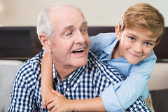 Happy little boy embracing senior grandfather (carlosgomes27) Tags: people adult portrait man male senior old aged elderly mature caucasian young child boy family grandfather grandson grandchild grandparent smiling cheerful happy embracing hugging cuddling relationship bonding love casual indoor face positive expression retirement retired pensioner looking together childhood kid togetherness generation lifestyle home emotion joy sitting elementary affection