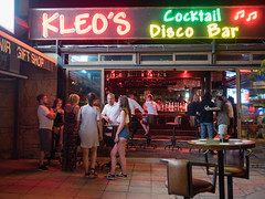 Kelo's (Howie Mudge LRPS BPE1*) Tags: kelos coralbay cyprus men women people candid casual portrait photography photographer snapshot bar busy neonlights table stool chair travel travelling traveller outside outdoors holiday vacation street streetphotography streetlife streetstyle olympus olympusuk microfourthirds mft m43 compactsystemcamera mirrorlesscamera olympusm17mmf18