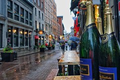 Rained out patios on rue Saint-Paul in Montreal (beyondhue) Tags: montreal vieux rue saint paul rain champagne street shot quebec beyondhue cobblestone patio table weather travel people umbrella wet water drop