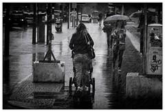 Summer in the city (frodul) Tags: berlin regenschauer natur wetter regen frau kinderkarre regenschirm leipzigerstrase outdoor bw einfarbig monochrom sw street passant mensch sommer strase deutschland
