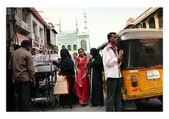 walk this way (handheld-films) Tags: india hindu muslim woman women street candid portrait portraiture people red sari black niqab burka burqa smile bright indian subcontinent city cities coexistence harmony anticipation hyderabad yellow tuktuk group minarets narrow
