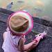 Kleinkind mit Hut füttert Fische