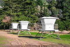 Daytime exterior photo of row of lifeguard stations on California beach with mountain in background (Travis Powers Photography) Tags: california beach lifeguardtower lifeguard daylight
