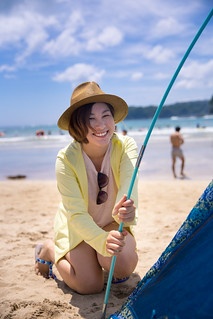 Happy young woman setting up tent on beach