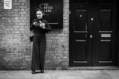 Multitasking (Cliff.j) Tags: girl food phone shoreditch brick lane london street candid shop eye contact wall standing look holding sony a7 mirrorless carl zeiss sonnar 55mm
