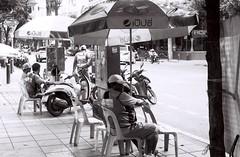 They Wait to Serve (35mm) (jcbkk1956) Tags: pentax pentaxk2 ilford ilfordpan100 manualfocus street bangkok thailand thonglo mono blackwhite analog 35mm film motorcycle motorcycletaxi riders streetfurniture umbrella worldtrekker