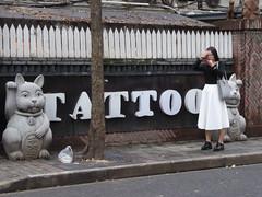 Should I do one... (Pavlov'sDog) Tags: shanghai china tatoo tatuaje calle caminar mujer women walking phone telefono celular street statue cat gato estatua purse cartera