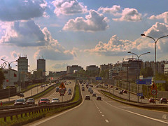 back to the city life (Ola 竜) Tags: way ride cityscape highway road sky clouds sunny cars vehicles traffic buildings skyscrapers streetlights street lampposts green lawn bridge architecture urban modern bluesky skyscape horizon perspective driverspov drive hot summer heat asphalt gritty noisy warmtones