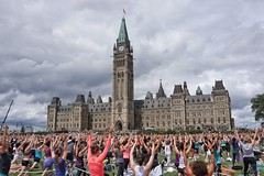 Reach for the sky...Parliament yoga. (beyondhue) Tags: yoga pose parliament hill lawn people building activity beyondhue summer class instruction peace tower flag warrior ottawa ontario canada downtown
