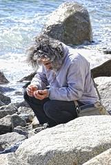 man with the sea stones (Vasiliy Marinka) Tags: man sea stones waves hands okhotsk