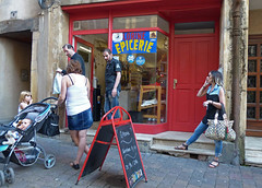 un jour dans la vie (Andy WXx2009) Tags: candid shop streetphotography store doorway advertising outdoors people shopping urban windows women men bags mobilephone talking meeting jeans pram femme children baby fashion style girls brunette sandals metz france europe motherhood