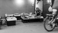 Simple life (Go-tea 郭天) Tags: pékin beijingshi chine cn street urban city outside outdoor people bw bnw black white blackwhite blackandwhite monochrome naturallight natural light asia asian china chinese canon eos 100d 24mm prime beijing hutong gulou market business job duty busy work working woman old lady vegetables fruits boxes floor ground bike bicycle candid portrait seller alone lonely poor plastic bags door open opened mobile phone cell cellphone cellular connected connexion data no network client customer borring borred simple