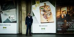 Chiswick Park (chrissarjeant) Tags: london chiswick station 85mm 18 candid sharplydressed streetphotography billboards portrait environmentalportrait