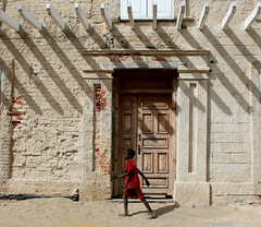 passing by in red (daniel.virella) Tags: boy red street house door shadows decay oldtown senegal saintlouis worldheritagesite unesco picmonkey