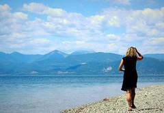 Day 202 : Is for ... The Little Black Dress (Storyteller.....) Tags: woman dress black little blonde walking beach blue sky sea greece people behind 365 deep365 summer vacation