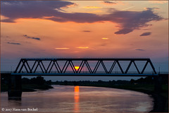 The sun caught in the bridge! (Hans van Bockel) Tags: 1680mm avond bridge brug deventer exposure hansvanbockel ijssel lightroom long lucht nef nikon photoshop raw rivier spoorbrug wolken thenetherlands nld zon zonsondergang railwaybridge