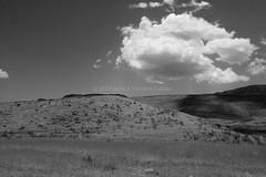 Namibian desertscape. (annick vanderschelden) Tags: namibia hardap naukluft mountains hills sand rocks arid semiarid desert vegetation grasses sky bluesky clouds sunlight hot soil dust bush cloud