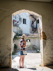 Tourist (Howie Mudge LRPS BPE1*) Tags: woman building architecture arch archway bright sunny day oldtown paphos cyprus light shade travel travelling traveller holiday vacation explore exploring hat olympus olympusuk microfourthirds mft m43 compactsystemcamera mirrorlesscamera olympusem5markii em5mkii olympusm17mmf18