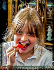 Day 194. (lizzieisdizzy) Tags: colour color child girl female pretty young eating snacking food sweet sweety happy fairhair blondblonde attractive girly laughing blouse shirt hold holding sweetie sugar smile smiling frame framed indoors inside