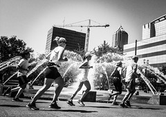 Ring Around The Fountain (TMimages PDX) Tags: iphoneography photography image photo photograph streetscene fineartphotography geotagged people urban city street streetphotography portland pacificnorthwest sidewalk pedestrians buildings avenue road blackandwhite monochrome vignette summer runners running park fountain water