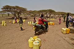 Boda boda driver carries water for earning income (Noel Molony) Tags: