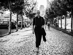 (graveur8x) Tags: man street streetphotography barefoot blackandwhite monochrome mann glasses contrast city people trees cobblestone lumix lumixgx80 panasonic panasonicdmcgx80 45mm olympusm45mmf18 zuiko dof