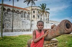 Boy with a canon (Pejasar) Tags: palmtrees grass clouds sky africa westafrica ghana elmina slavefortress castle canon boy