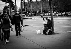 Passing by.. (Rabican7) Tags: california sanfrancisco streetphotography musician street bw monochrome blackandwhite people pedestrian trip travelling photography urban asian music performer instrument sad