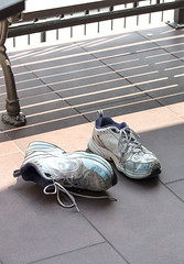 Old used tennis shoes laying on a concrete floor (Transient Eternal) Tags: tennisshoes shoes footware clothing dirtyshoes usedshoes usedfootware wornshoes worntennisshoes laces tiedlaced rubbersoles runningshoes runner walker sidewalk pavement bench seating oldshoes