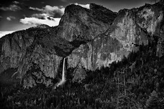 The Majestic Peaks of Cathedral Rock, Sentinel Point, and Half Dome (Black & White, Yosemite National Park) (thor_mark ) Tags: nikond800e lookingeast day6 triptopasoroblesandyosemite yosemitenationalpark capturenx2edited colorefexpro tunnelview pacificranges sierranevada yosemiterittersierranevada centralyosemitesierra yosemitevalley outside trees hillsideoftrees blueskieswithclouds mountains mountainsindistance mountainsoffindistance nearsunset sunsettime sunsetlight evergreens landscape nature bridalveilfall cathedralrocks falls waterfall waterfalls 617ft188metres ahwahneecheenamepohono spiritofthepuffingwind mountainside sentinelpoint sentinelrock project365 blackwhite silverefexpro2 california unitedstates