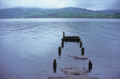 jetty (Ron Layters) Tags: lake woodenpoles jetty oldjetty distressed water windermere boat rain badweather windermerelakecruiser hills lakedistrict hawkshead cumbria lakedistrictnationalpark england slidefilmthenscanned slide transparency fujichrome velvia leica r6 leicar6 ronlayters