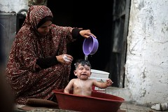 A Palestinian mother showering her baby in a bowl during a heatwave in Gaza City (TeamPalestina) Tags: freepalestine palestinian sunrise sweet beautiful heritage live photo photographer comfort natural تصويري palestine nice am amazing innocent occupation landscape landscapes reflection blockade hope canon nikon