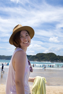 Happy young woman looking over shoulder on beach