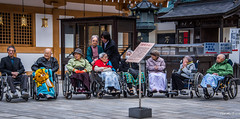 2017 - Japan - Aomori - Big Buddha Visitors (Ted's photos - For Me & You) Tags: 2017 aomori cropped japan nikon nikond750 nikonfx tedmcgrath tedsphotos vignetting seiryujitemple aomorijapan wheelchairs old oldpeople people peopleandpaths blankets lanterns elderly oldfolks aged oldmen oldwomen glasses wheels seating seated seats sitting wideangle widescreen hats hat