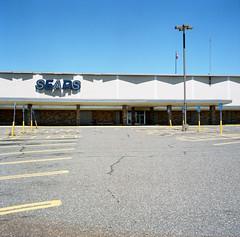 sears (kaumpphoto) Tags: rolleiflex tlr sears building parkinglot sky handicapped parking flag brick shadow sign asphalt capitalism store retail saintpaul
